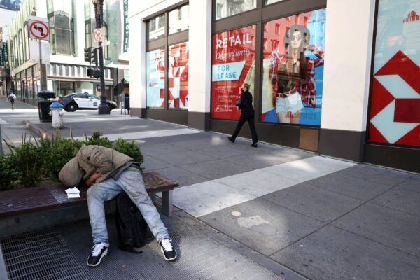 A homeless person sleeps on a bench
