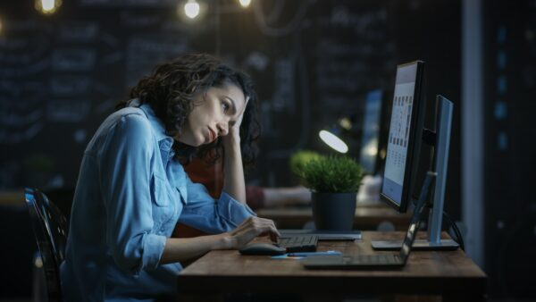A tired woman works at her computer