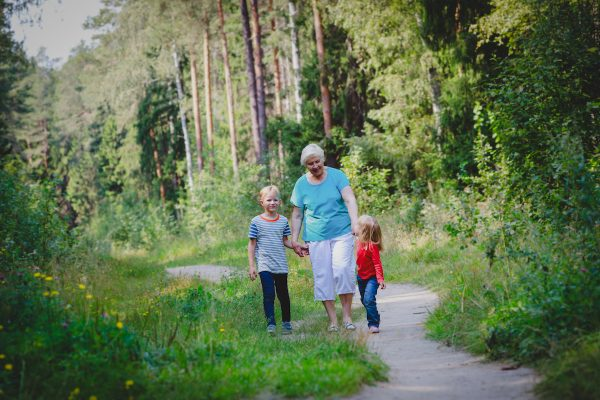 happy senior grandmother with kids walk in nature